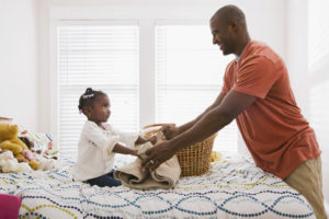 Father and Daughter folding clothes